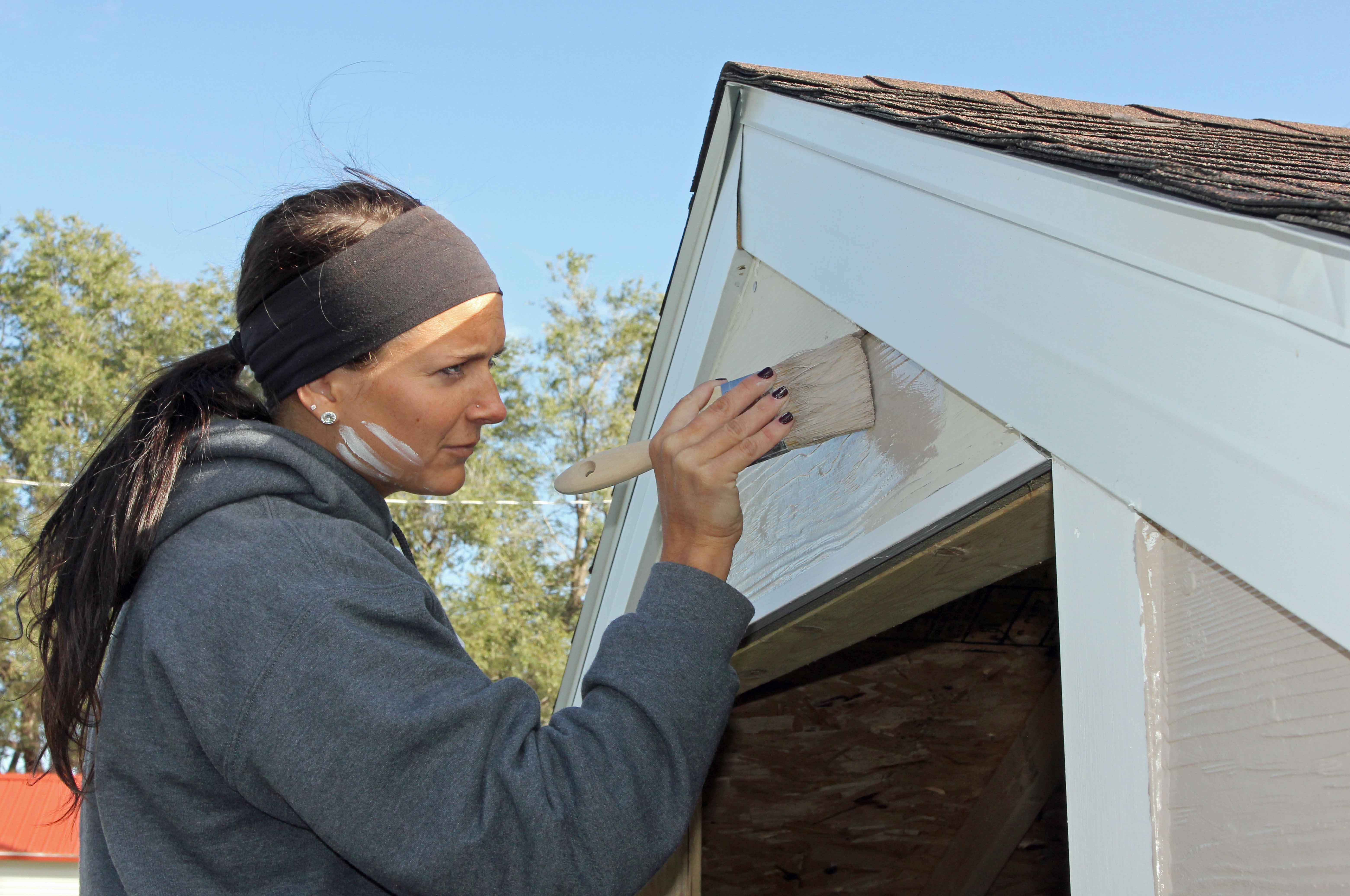 UNK softball player Kenzie Helmink paints a storage shed as part of the team's volunteer efforts with Habitat for Humanity. (Photo by Todd Gottula/UNK Communications)