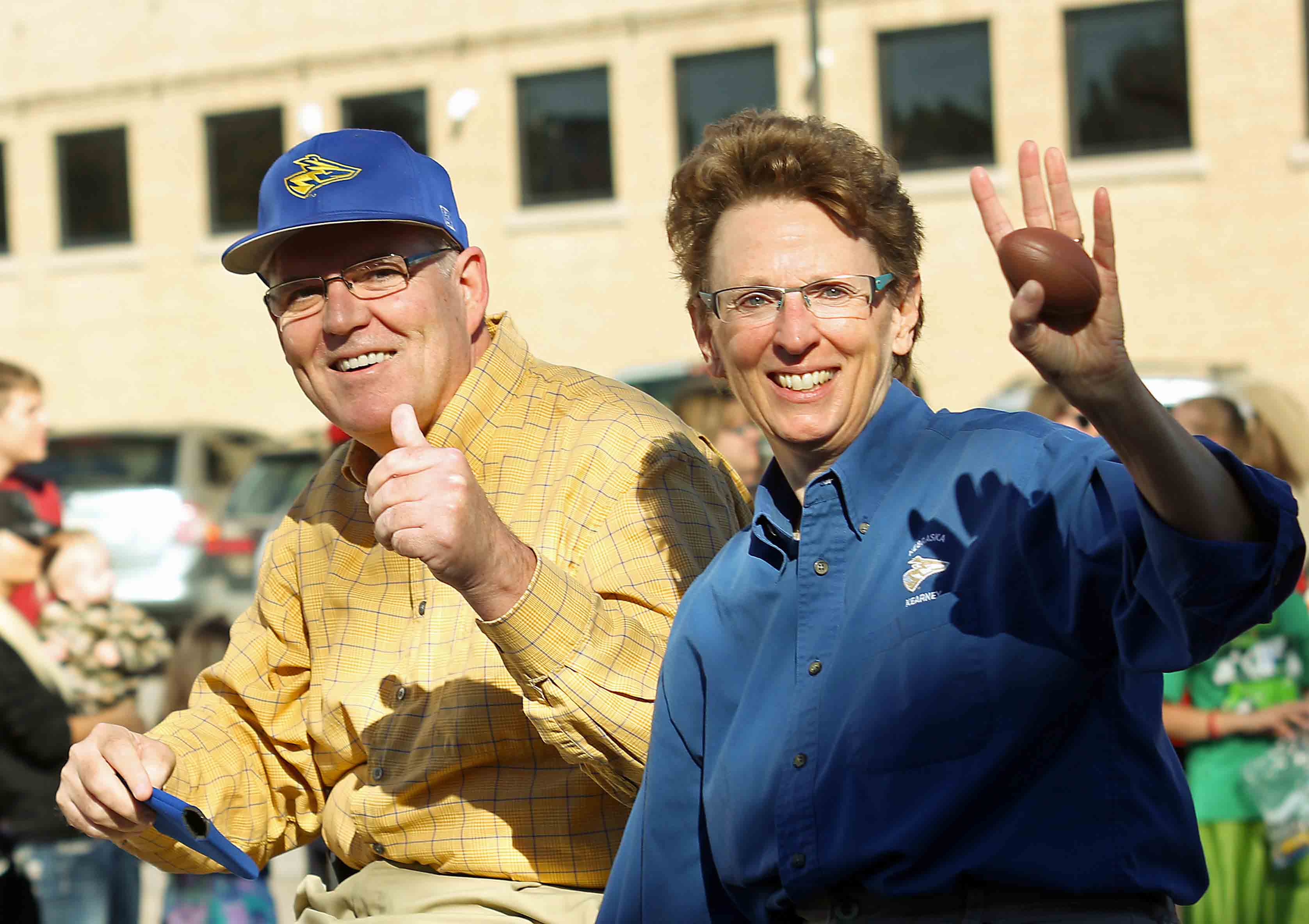 "Jon McBride and his wife, Karen, ride in the 2013 UNK Homecoming parade. McBride was diagnosed with Parkinson's disease in 2009. ""People are used to Jon McBride pre-Parkinson's, and now there's Jon McBride with Parkinson's,"" he said. ""It's different. I don't walk the same, I don't move as quickly, I'm not as expressive. So I've changed. So be it. That's where we are, and now we move forward."" (Photo by Todd Gottula/UNK Communications)"