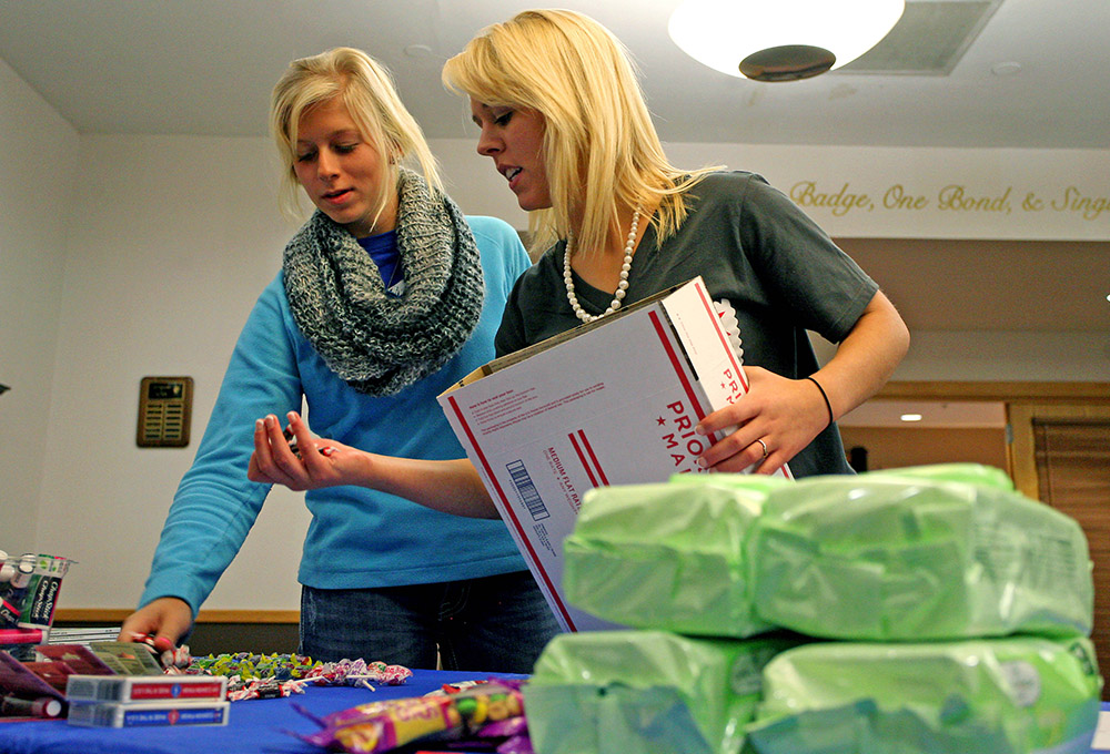 Alpha Omicron Pi's Courtney Hayden, left, and Jillian Stoumbaugh fill care packages for deployed troops during the Sisters for Soldiers event at UNK. The sorority is sending 150 care packages to soldiers overseas. (Photo by Sara Giboney/UNK News)