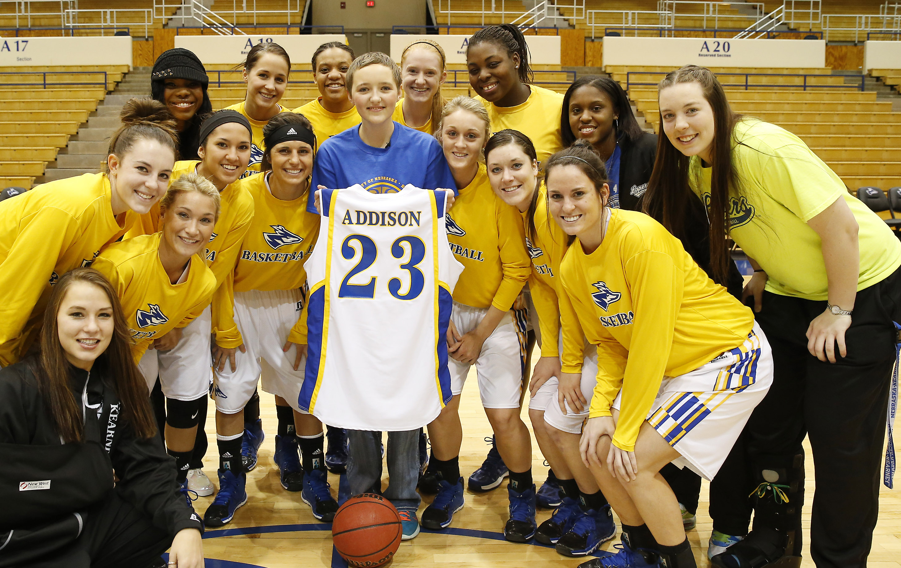 Members of the University of Nebraska at Kearney women's basketball team present Addison Samuelson with a team jersey Friday. Samuelson was named an honorary member of the team following surgery to remove a cancerous brain tumor. She is a sophomore at Cambridge High School. (Photo by Corby R. Dorsey/UNK Communications)