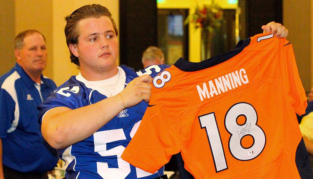 Offensive lineman Derek Hill of Gretna displays a signed Peyton Manning jersey during Tuesday's live auction. Manning's jersey brought in a winning bid of $1,900.