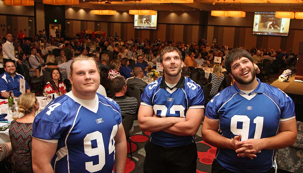 UNK defensive lineman, from left, Sam Stoltenberg, Matt Bowman and Jack Wardyn react to a video presentation at Tuesday's Loper Football Backers Club dinner and fundraiser.