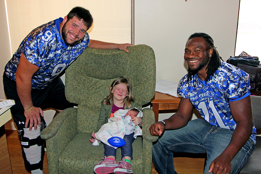UNK defensive lineman Jack Wardyn (91) and running back Romero Cotton (11) visit TayLee Donahoo and her newborn brother, Trysten, Monday at CHI Health Good Samaritan in Kearney. TayLee and Trysten are the children of Alysha Donahoo of Kearney.