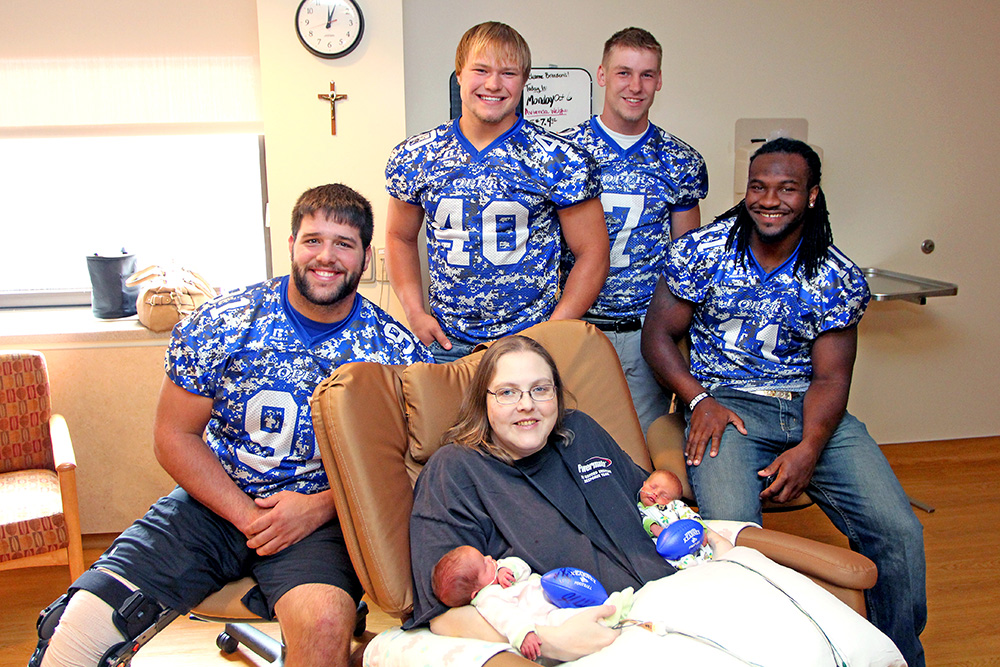 Stacy Breeden of Kearney and her newborn twins, Avienda and Dylan, received autographed footballs and a visit from UNK team captains, left to right, Jack Wardyn, Tyke Kozeal, Bronson Marsh and Romero Cotton.
