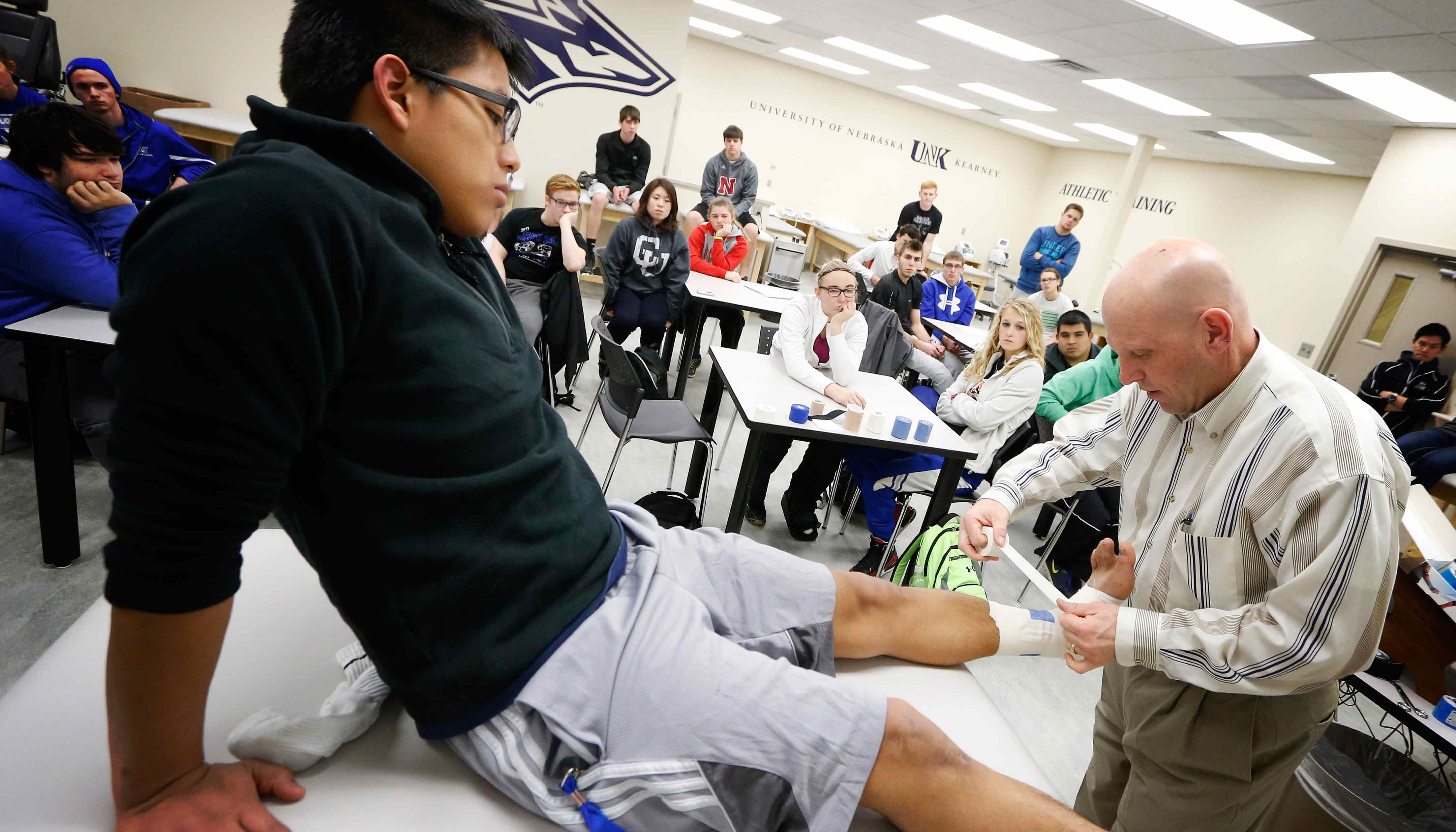 Scott Unruh, professor of kinesiology and sport sciences at UNK, instructs students on taping ankles inside the new athletic training classroom and lab.