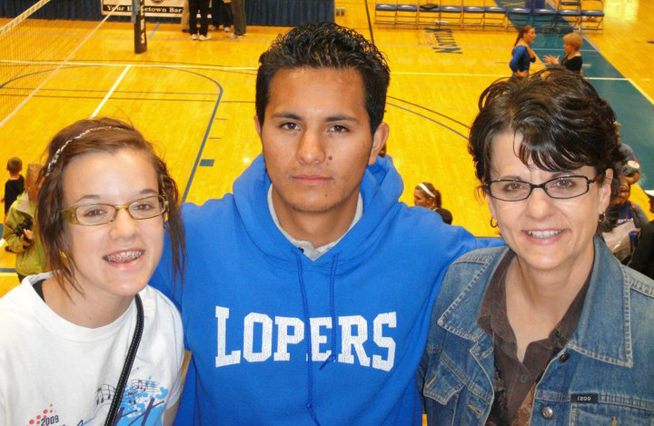 UNK International Education Outreach Coordinator Bonnie Payne (right) and her daughter, Kristin, attend a Loper basketball game with Carlos Rodriguez of Bogota, Colombia, as part of the International Friendship Program.