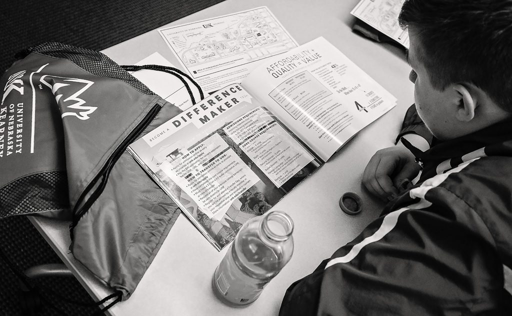 9:58 a.m. - Shortly after arriving on campus, Nikolas Gligorevic of Seward looks over UNK's Campus Guide and other information while waiting for an admissions presentation to begin.