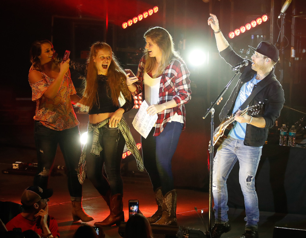 UNK students, from left to right, Karissa Finke of Ravenna, Jenna Gillespie of Holdrege and Kennedy Sander of Lincoln dance on stage with Parmalee's Matt Thomas at Thursday's Loper Programming and Activities Council spring concert. The show at UNK's Health and Sports Center also included opening act Logan Mize and headliner Joe Nichols. (Photo by Corbey R. Dorsey/UNK Communications)