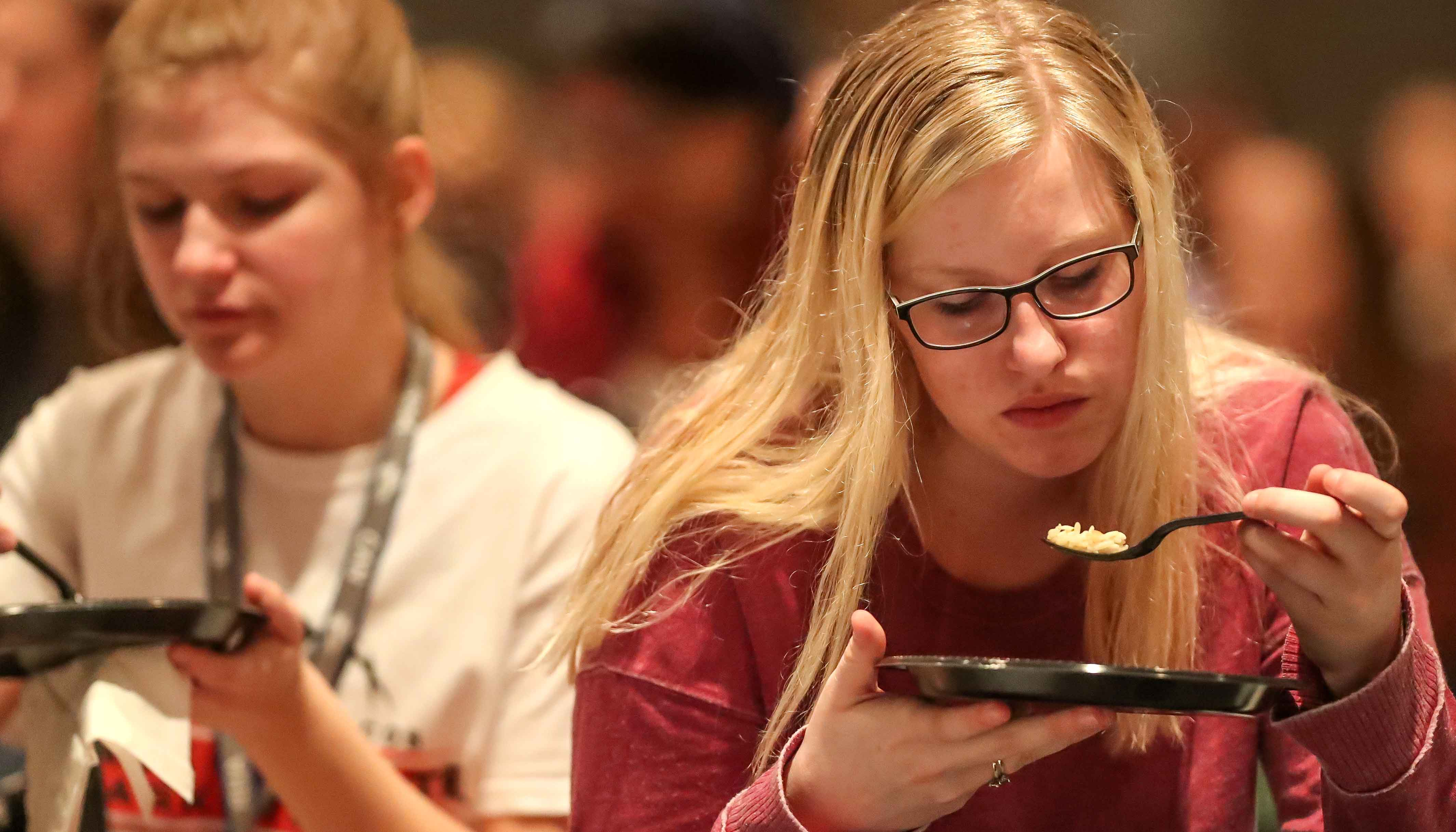 UNK students Kenna Storrs of Kearney, left, and Maddie Good of Gothenburg participate in the Hunger Banquet Tuesday. The event raised awareness about hunger and food insecurity in the United States and Kearney community. (Photo by Corbey R. Dorsey/UNK Communications)