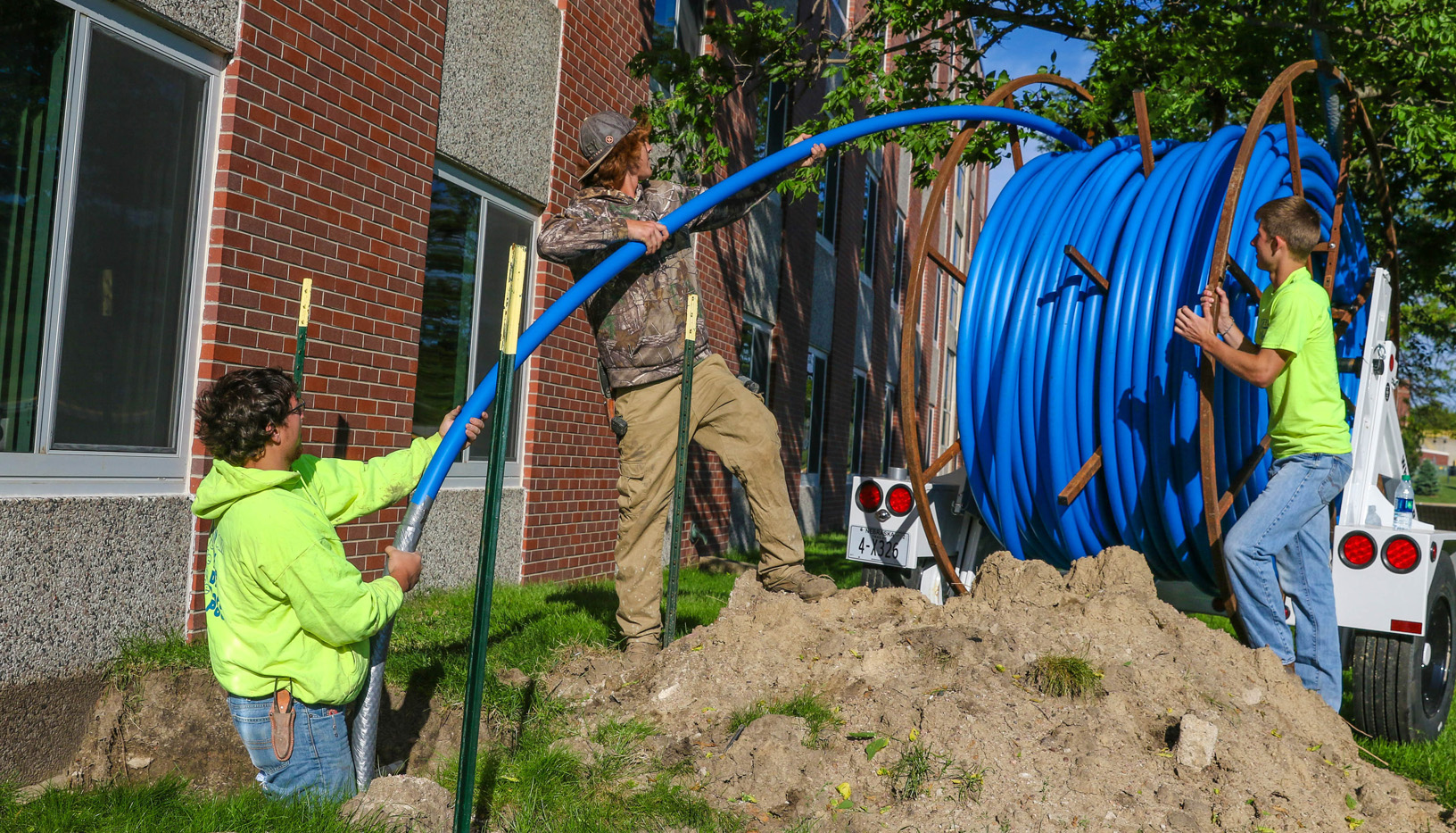 Myers Construction of Broken Bow workers, from left, Jake McCormick, Slade Russell and Collin Hoffman roll out tubing that is part of new fiber optic ring installation that will improve information technology services at UNK. (Photo by Corbey R. Dorsey/UNK Communications)
