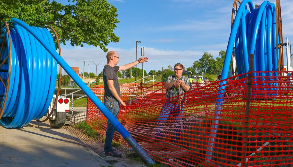 UNK Network Analyst Rick Mollard, left, and Director of Information Technology Services Brian Cox look over a trench near Cope Stadium, which will house a new fiber optic ring and improve the availability of information technology services on campus. (Photo by Corbey R. Dorsey/UNK Communications)