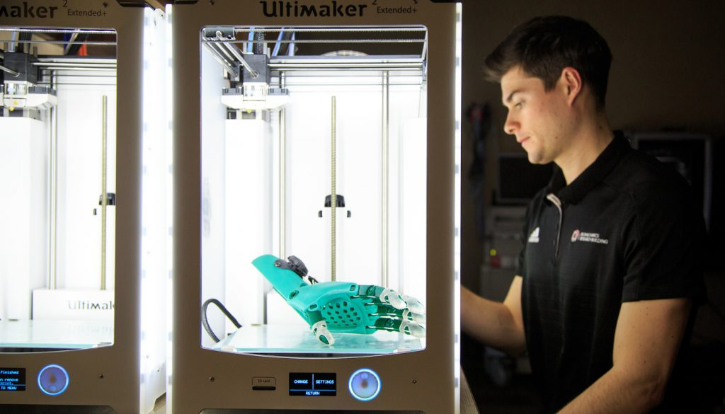 """Drew Dudley, a biomechanics graduate assistant and biomedical engineer, programs a 3D printer inside the robotics laboratory at UNO. A team of University of Nebraska researchers believe they can design a 3D-printed arm prosthesis that would cost under $1,000 in parts."
