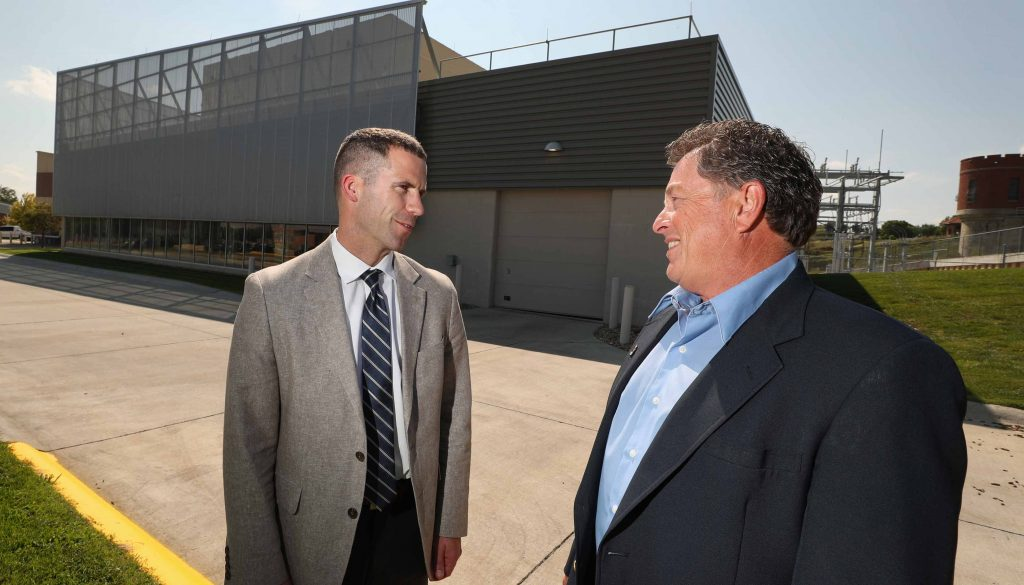 UNK's Jon Watts, left, and NPPD's Stan Clouse discuss the agreement that soon will give the university 25 percent of its electrical energy from the new $11 million solar park being built in Kearney. (Photo by Corbey R. Dorsey/UNK Communications)