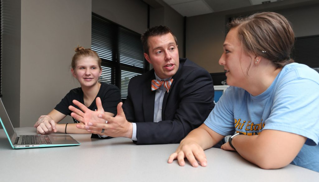 Ben Malczyk, assistant professor of social work, discusses UNK's new online social work programs with students Kenna Storrs of Kearney, left, and Hannah Brown of Scottsbluff. (Photo by Corbey R. Dorsey, UNK Communications)