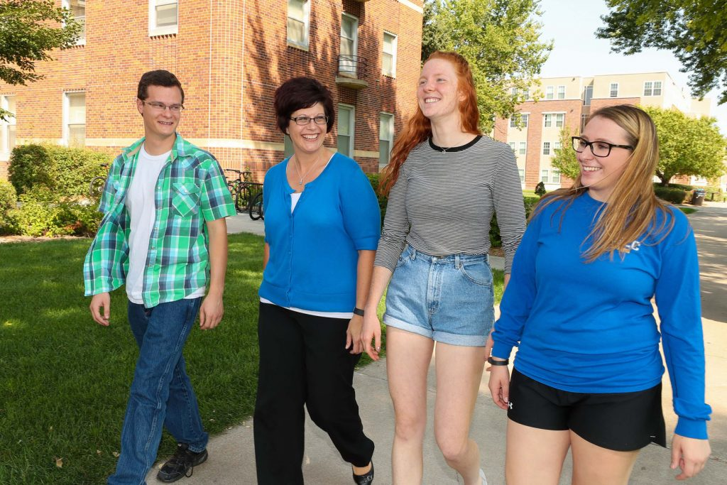 UNK Thompson Scholar students, left to right, Luke Hamilton of Bridgeport, Keanna Kroeker of Fairbury and Hannah King of Central City visit with the program's director, Jennifer Harvey, while walking across campus. (Photo by Corbey R. Dorsey/UNK Communications)
