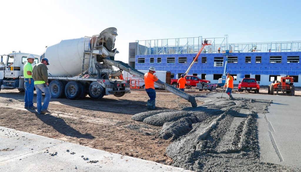 Workers pour the parking lot Wednesday at the new Village Flats residence hall at UNK. The $16 million project is planned for completion in July 2018. (Photo by Corbey R. Dorsey, UNK Communications)