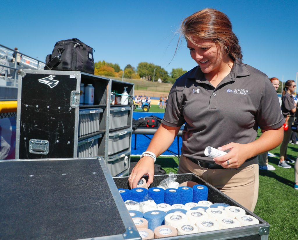 Amber Bendig, an athletic training major from Naper, prepares equipment prior to a recent Loper football game. In fall 2018, UNK is adding a Master of Athletic Training degree. (Photo by Corbey R. Dorsey/UNK Communications)