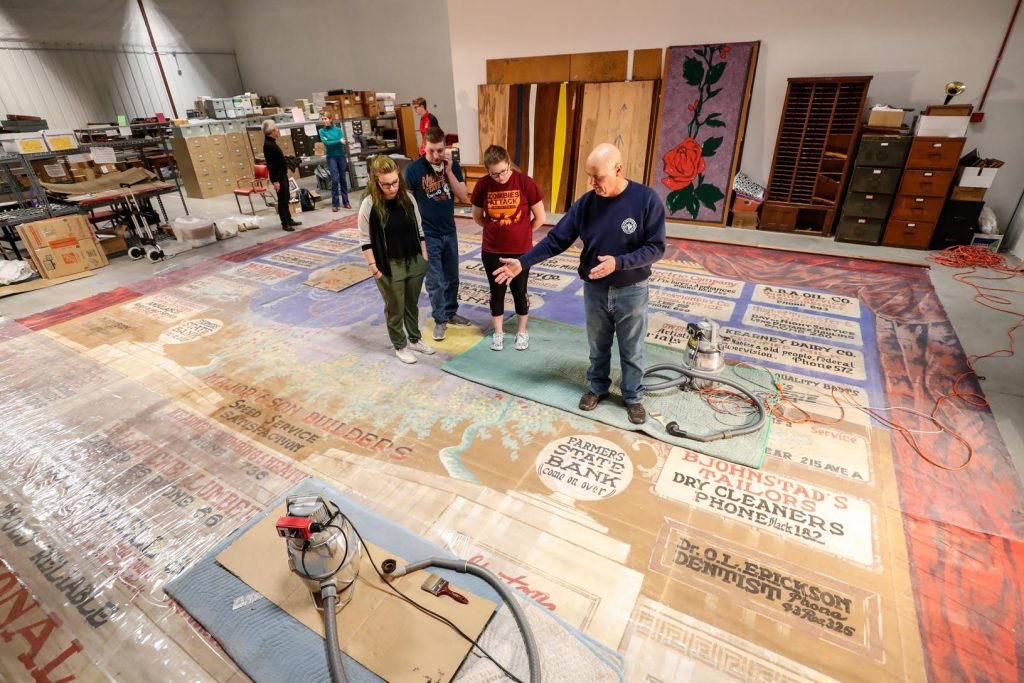 UNK student Allan Osburn, far right, discusses restoration details of the Kearney Opera House curtain while standing in the middle of the project with fellow students, left to right, Sydney Engel, Ned Purdy and Katy Anielak. (Photo by Corbey R. Dorsey, UNK Communications)