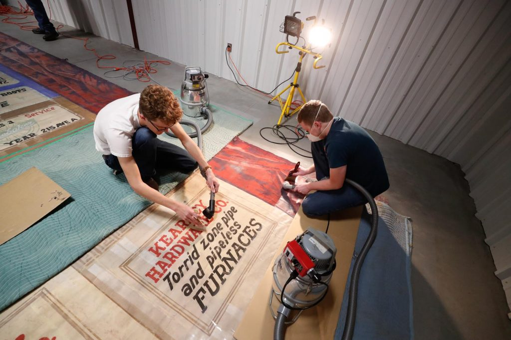 UNK students Brandon Wamberg, left, and Ned Purdy, right, work on a section of the Kearney Opera House curtain, which eventually will be displayed at Buffalo County Historical Society's Trails & Rails Museum. (Photo by Corbey R. Dorsey, UNK Communications)