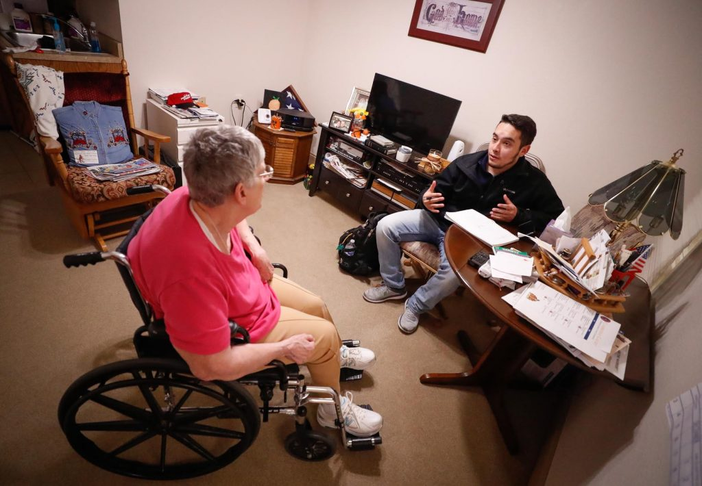 Cambridge Court resident Gayle Day visits with Ruben Meza Jr. of Wood River in her apartment. Meza is one of nine UNK students studying this semester at Cambridge Court, where they meet one-on-one and conduct psychosocial assessments of elderly residents. (Photo by Corbey R. Dorsey, UNK Communications)