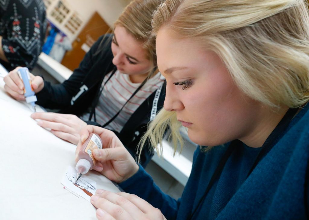 Overton students Jaycee Wallace, right, and Sidney Enochs take part in a ceramics surfacing demonstration at Wednesday's Imagination Day at the University of Nebraska at Kearney. (Photo by Corbey R. Dorsey, UNK Communications)