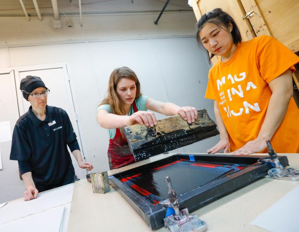 Professor Victoria Goro-Rapoport, left, and University of Nebraska at Kearney student Lim Yun Ji of Korea, right, work with Morgan Boldt of Amherst on a printmaking project Wednesday at UNK's Imagination Day. (Photo by Corbey R. Dorsey, UNK Communications)