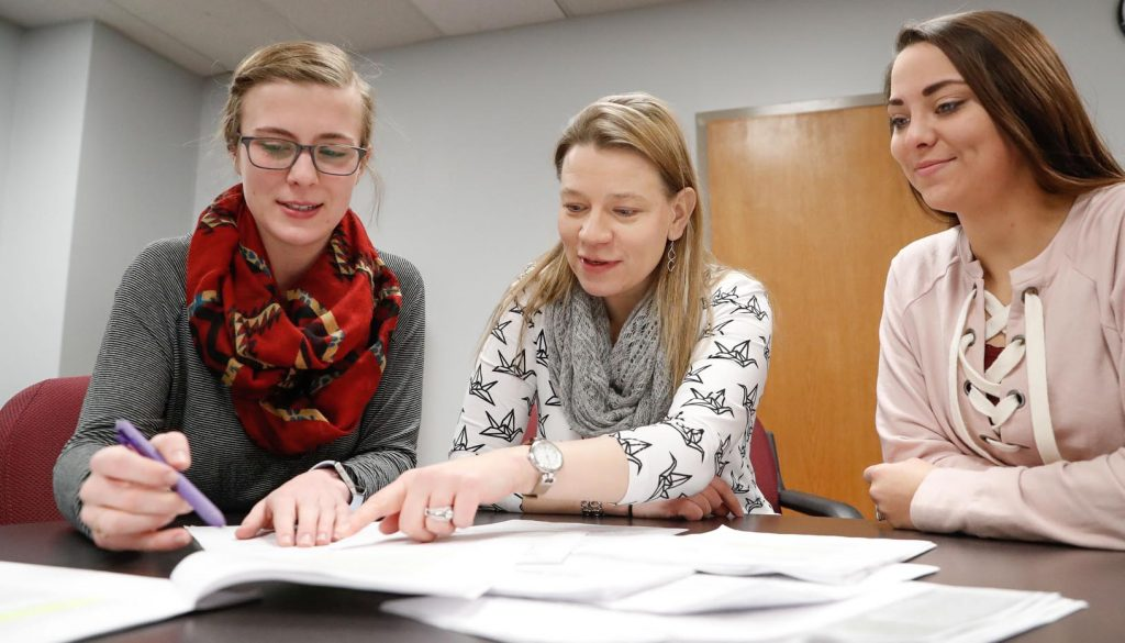 University of Nebraska at Kearney ad campaigns students Madeline Maloley, left, and Rachel Smith, right, work on a project for Nebraska School of Martial Arts with Assistant Professor Sonja Bickford. (Photo by Corbey R. Dorsey, UNK Communications)