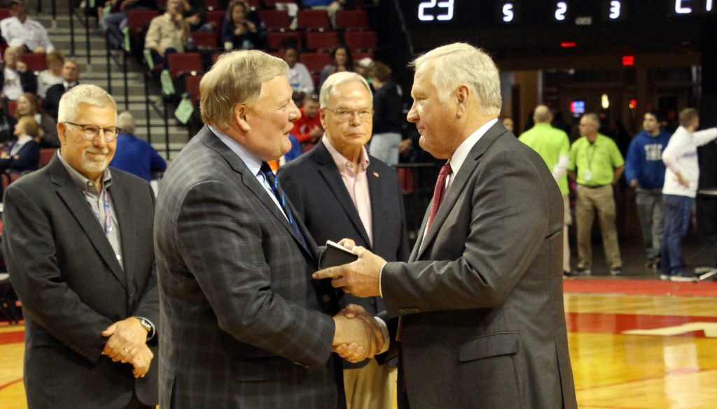 UNK Chancellor Doug Kristensen receives the NSAA Distinguished Service Award from the NSAA's Jim Tenopir at halftime of Saturday's Class A boys basketball state championship game at Pinnacle Bank Arena. (Photo courtesy, Randy Gottula)