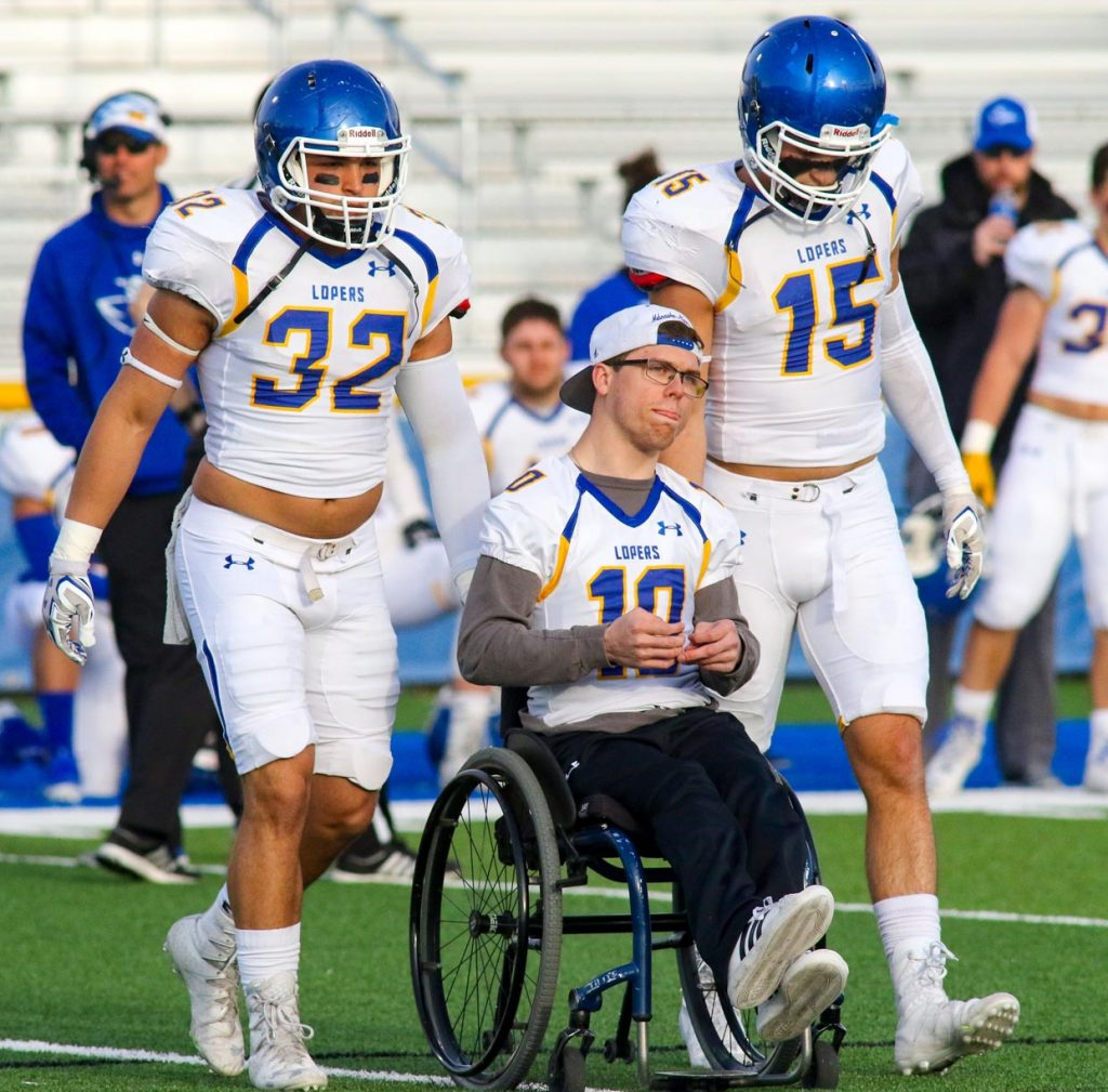 Linebackers Sal Silvio, left, and Zach Sullivan escort Andrew Dubowsky to midfield for the coin toss at UNK's spring game. Dubowsky, who was born with cerebral palsy, is a fixture at Loper football and wrestling events. (Photo by Todd Gottula, UNK Communications)