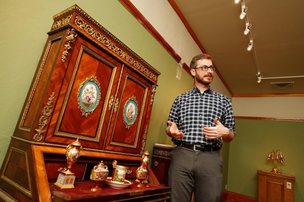 Will Stoutamire, director of the G.W. Frank Museum of History and Culture on the UNK campus, shows off a collection of decorative arts added as a permanent exhibit on the museum's second floor. (Photo by Corbey R. Dorsey, UNK Communications)