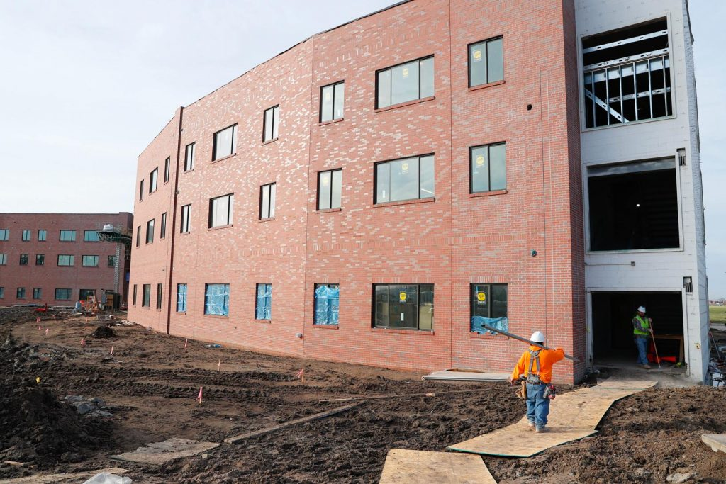 Crews are finishing masonry and brick work on the exterior facade, and soon will turn their attention to finishing the parking lot, installing sidewalks and landscaping work at the new Village Flats residence hall at the University of Nebraska at Kearney. (Photo by Corbey R. Dorsey, UNK Communications)