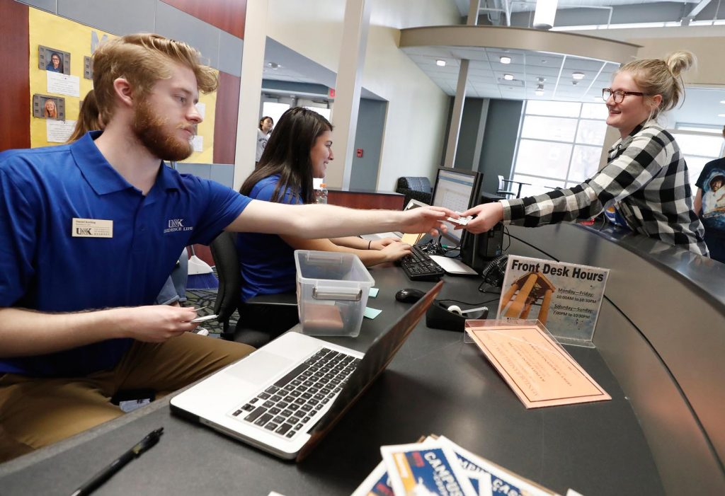 """Jayde McDowell, right, a freshman from Ravenna, works with Daniel Keeling from UNK Residence Life on Wednesday as she completes her checkout from Randall Hall. McDowell called her time in the residence hall a positive experience, """"because that's where I met all of my friends."""" (Photo by Corbey R. Dorsey, UNK Communications)"""