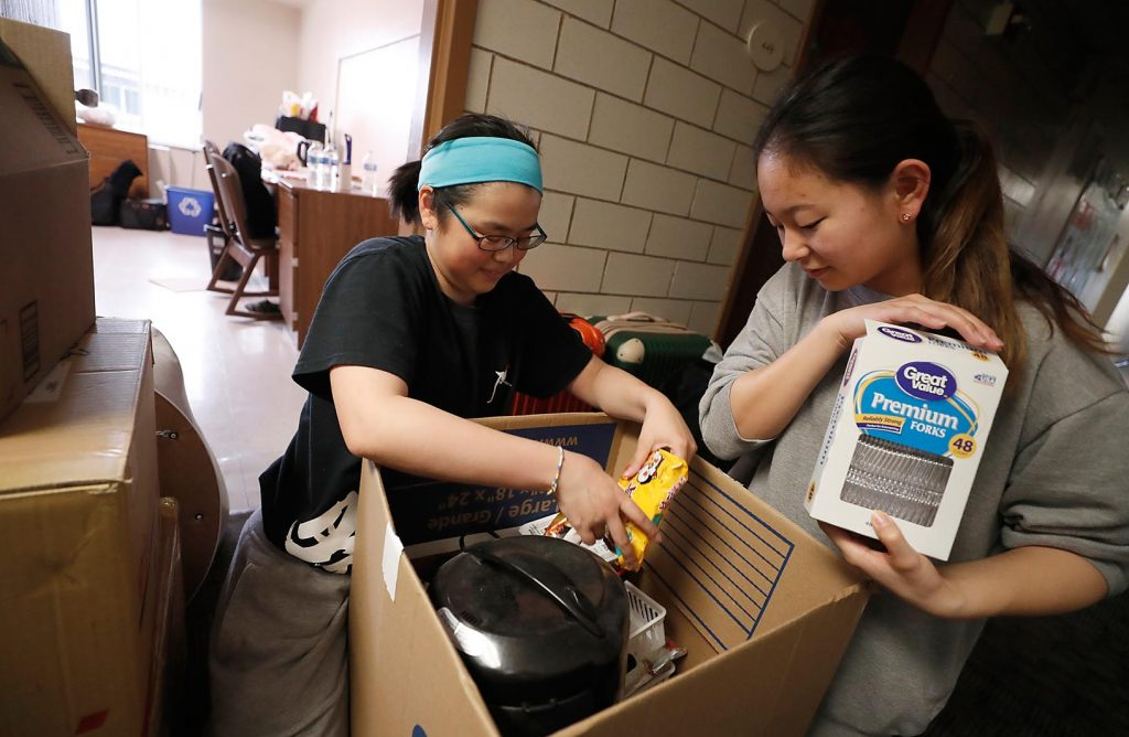 UNK students Suzuha Sasaki, left, and Mizuki Yoshino pack up their belongings Wednesday afternoon inside Randall Hall. It was a busy week across campus as students living in residence halls moved out for the summer. (Photo by Corbey R. Dorsey, UNK Communications)