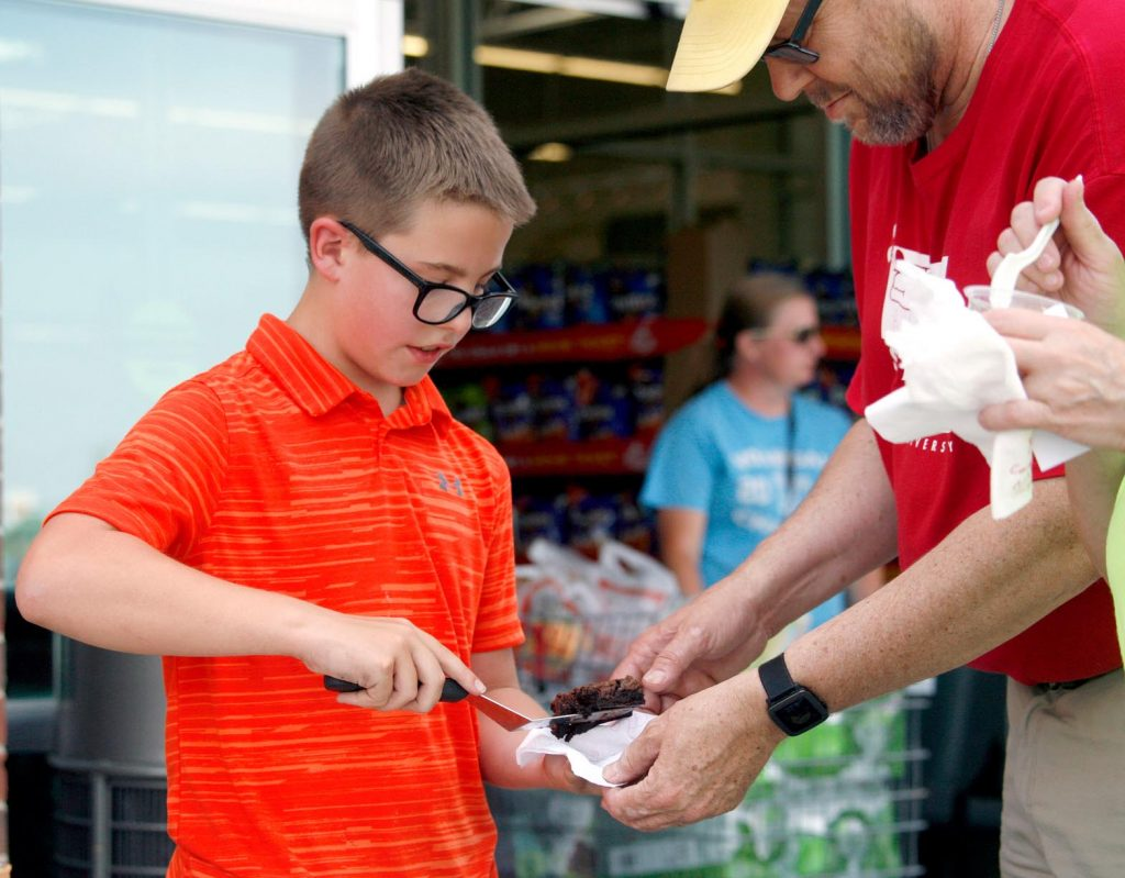 Tate Brown, 12, of Kearney, left, scoops out a brownie for a customer Friday evening during the Biz Kidz Camp product showcase at the Kearney Hy-Vee. (Photo by Tyler Ellyson, UNK Communications)
