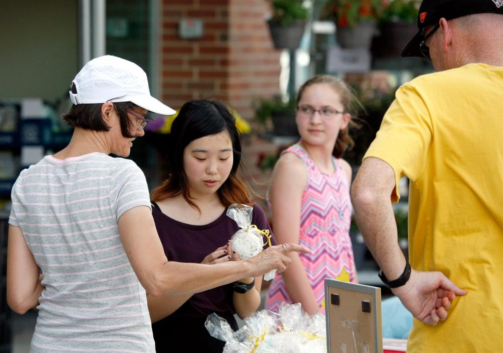 Thirteen-year-old Isabella Cao of Kearney, second from left, talks to customers about her handmade bath products Friday evening during the Biz Kidz Camp product showcase at the Kearney Hy-Vee. (Photo by Tyler Ellyson, UNK Communications)