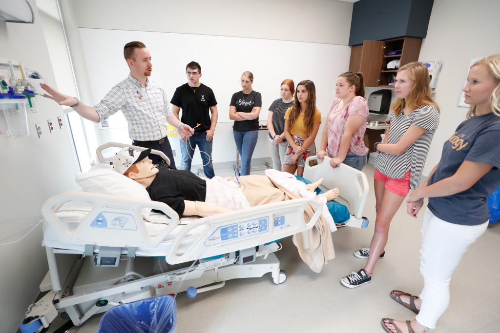 Doctoral student and UNMC College of Nursing faculty Douglass Haas, left, walks students through procedures such as administering shots, CPR and inserting a nasogastric tube using a training mannequin at the Health Sciences Academy at the University of Nebraska at Kearney. (Photo by Corbey R. Dorsey, UNK Communications)