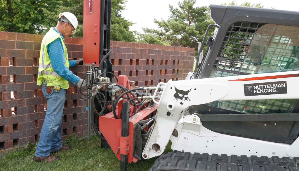 Nuttelman Fencing co-owner Keith Nuttelman, left, and employee Ben Seals install metal pipes Friday for the construction fence along the south side of UNK's Fine Arts Building, where work will take place over the next year as part of the Otto C. Olsen replacement project. (Photo by Corbey R. Dorsey, UNK Communications)