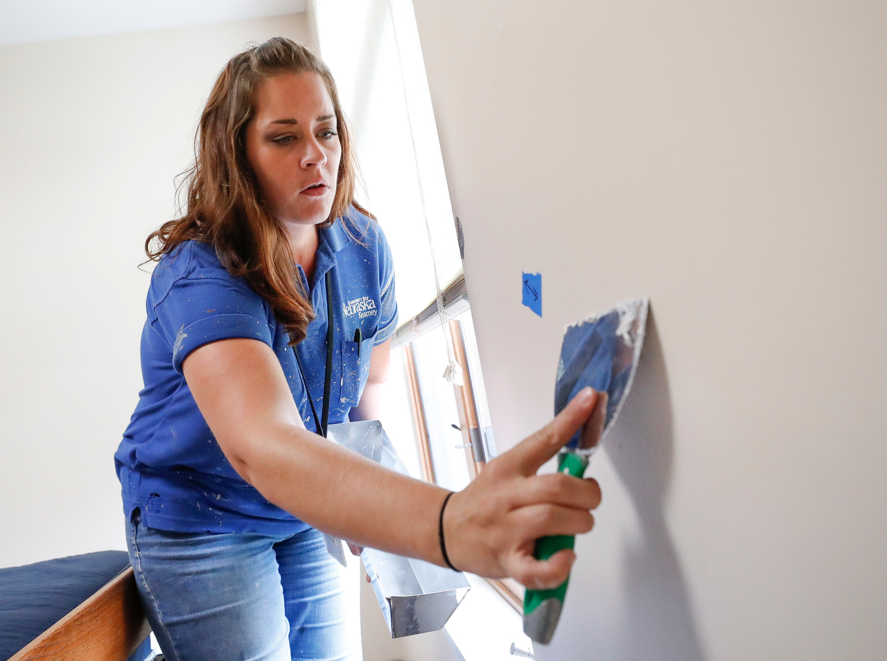 UNK Facilities Management employee Kelli Smith repairs a ding on a wall inside a residence hall.