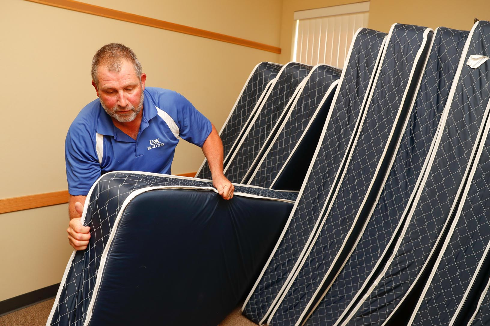 Dave White with UNK Facilities Management helps replace the mattresses inside a residence hall at the university. The used mattresses were donated to three charitable groups. (Photo by Corbey R. Dorsey, UNK Communications)