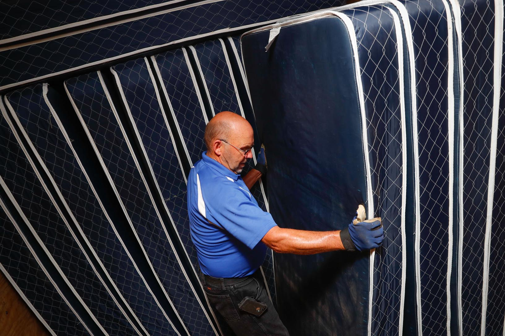 Don Wellensiek, surplus inventory manager with UNK Facilities Management, stacks mattresses inside a semitrailer headed to Orphan Grain Train in Norfolk. UNK donated 335 used mattresses to charitable groups, including Orphan Grain Train, as part of the inventory replacement process for three residence halls. (Photo by Corbey R. Dorsey, UNK Communications)