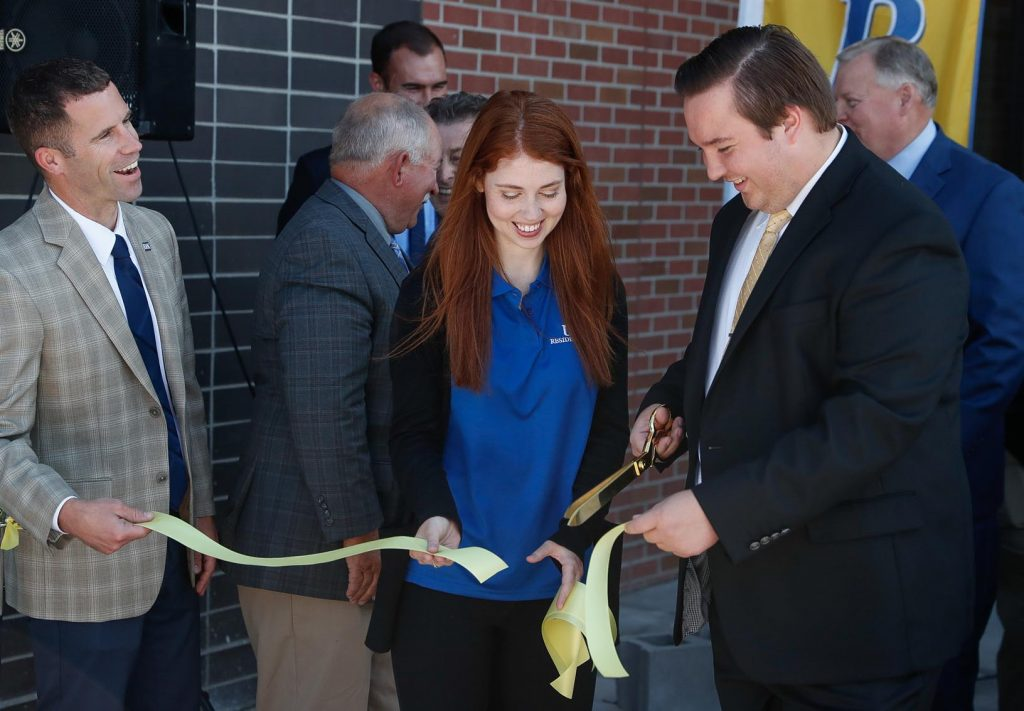 Front row, from left, Cacia Barnes with UNK Residence Life and Taylor Janicek, UNK student body vice president, cut the ribbon Tuesday to officially open Village Flats. The 130-bed, apartment-style residence hall is located in University Village, a new development south of UNK's West Center and the Health Science Education Complex. (Photo by Corbey R. Dorsey, UNK Communications)