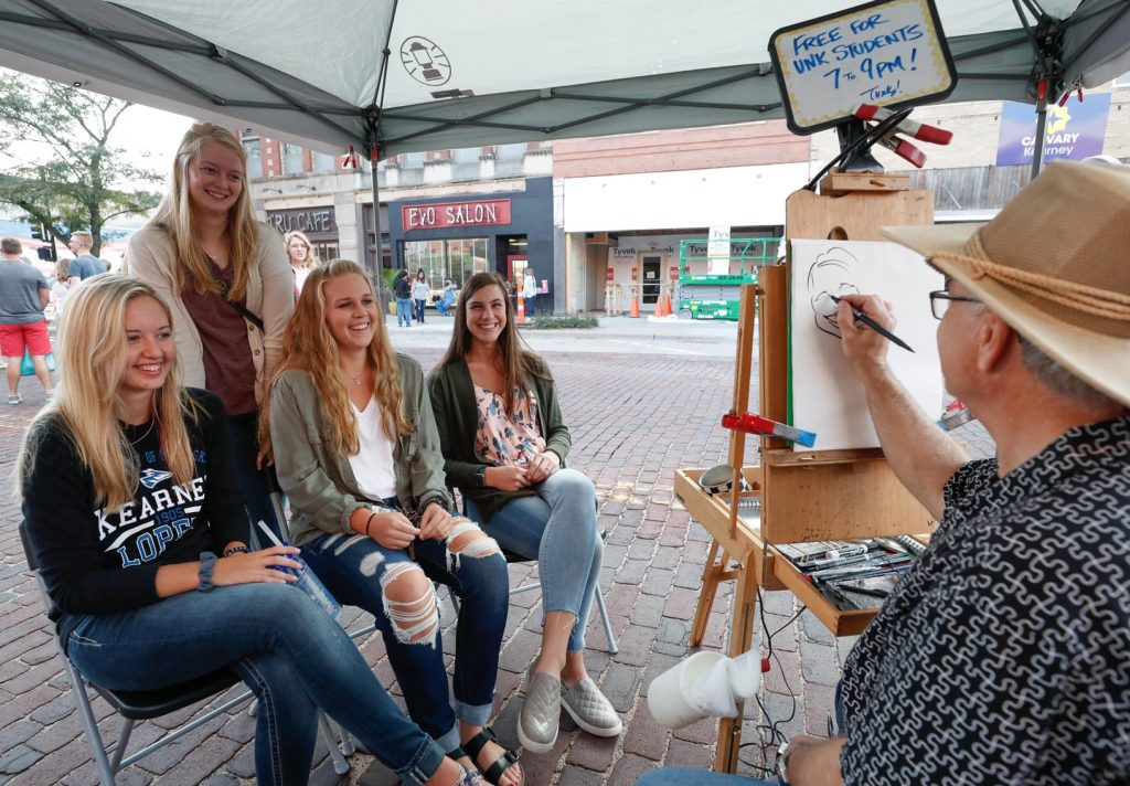 UNK students, from left, Whitney Walker, Madison Clausen, Joslyn Grabill and Sadie Svoboda get a caricature drawn by artist Dirk Christensen at Thursday's Destination Downtown event on The Bricks. (Photo by Corbey R. Dorsey, UNK Communications)