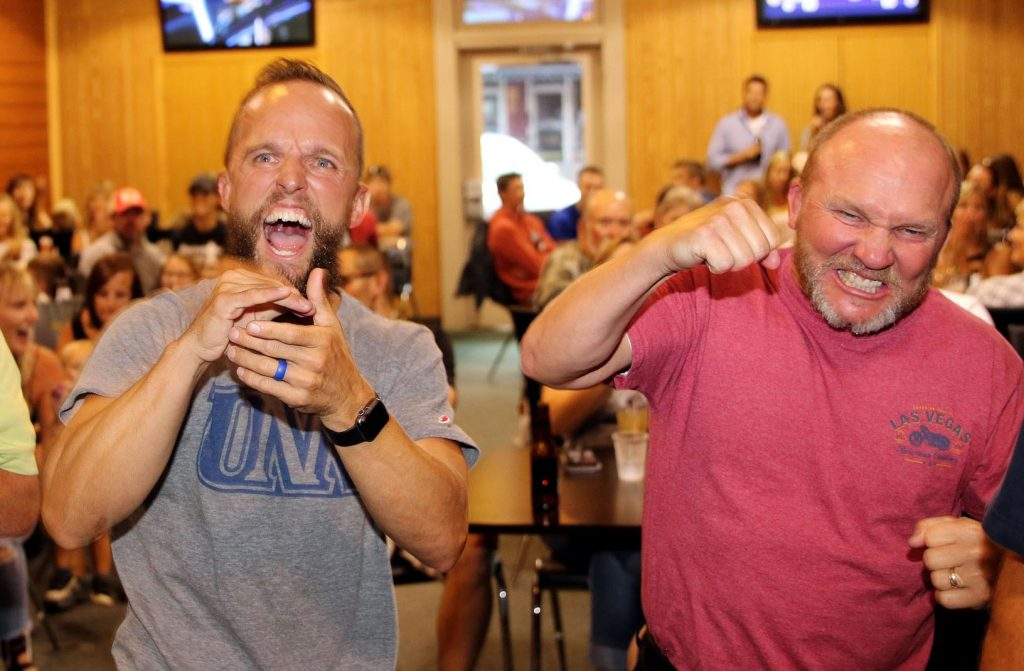 "Bryce Abbey, left, and friend Brian Hagan celebrate Friday as they watch a scene from the show ""TKO: Total Knock Out"" at a watch party in Kearney. Abbey, a professor at University of Nebraska at Kearney, won the episode and $50,000. (Photo by Todd Gottula, UNK Communications)"