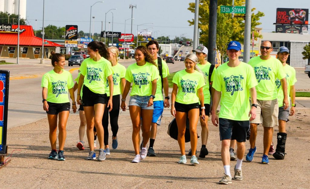 """Members of the Loper track and field team walk along Second Avenue in Kearney Saturday during UNK's """"Here Come the Lopers"""" event. More than 400 athletes, coaches and staff handed out team posters and schedules at businesses across Kearney. (Photo by Todd Gottula, UNK Communications)"""
