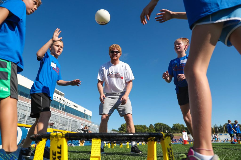 UNK wrestler Trey Schlender, center, guides an activity at Nebraska Kids Fitness and Nutrition Day. More than 800 fourth-grade students from central Nebraska attended Friday's event, learning about fitness and healthy eating. (Photo by Corbey R. Dorsey, UNK Communications)