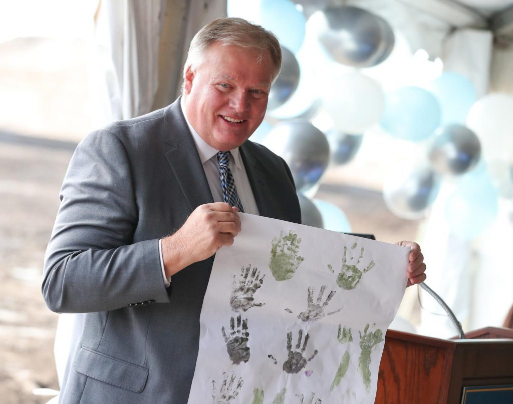 UNK Chancellor Doug Kristensen shows the audience a display of children's handprints as College of Education Dean Sheryl Feinstein talks about the importance of early childhood education Friday morning during a groundbreaking ceremony for UNK's new LaVonne Kopecky Plambeck Early Childhood Education Center. (Photo by Corbey R. Dorsey, UNK Communications)