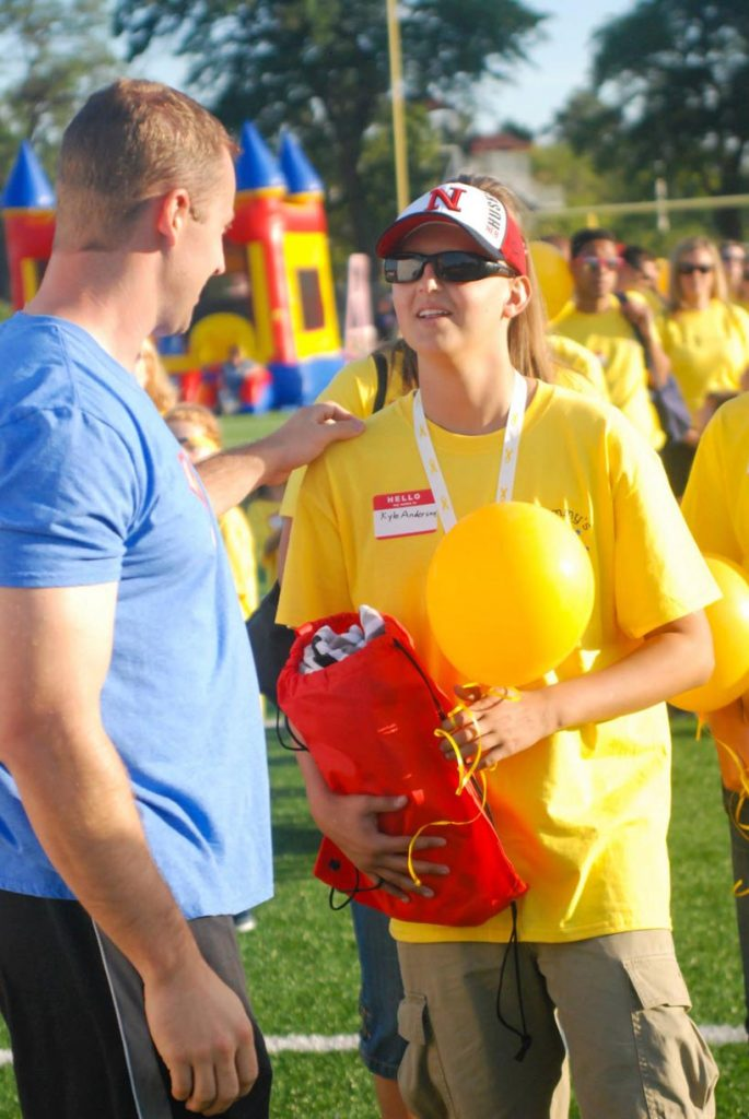 UNK sophomore Kyle Anderson, right, meets Olympic bobsledder Curt Tomasevicz during the 2015 Glow Gold event organized by Sammy's Superheroes Foundation, a Columbus-based nonprofit that raises money for childhood cancer research. Anderson, a Columbus native, was diagnosed with osteosarcoma in 2011. (Courtesy photo)