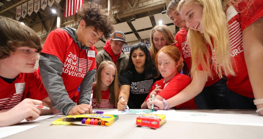 UNK student Tanya Wasson of Kearney, center, works with a team of high schoolers Thursday during New Venture Adventure at UNK. The event, hosted by the Enactus student organization, promotes entrepreneurship. (Photo by Corbey R. Dorsey, UNK Communications)
