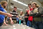 """UNK junior Shyann Cochrane, left, leads an """"odor identification"""" activity Tuesday during a psychology fair in the Nebraskan Student Union Ponderosa Room. Only a couple of high schoolers correctly identified all of the mystery scents. (Photo by Corbey R. Dorsey, UNK Communications)"""