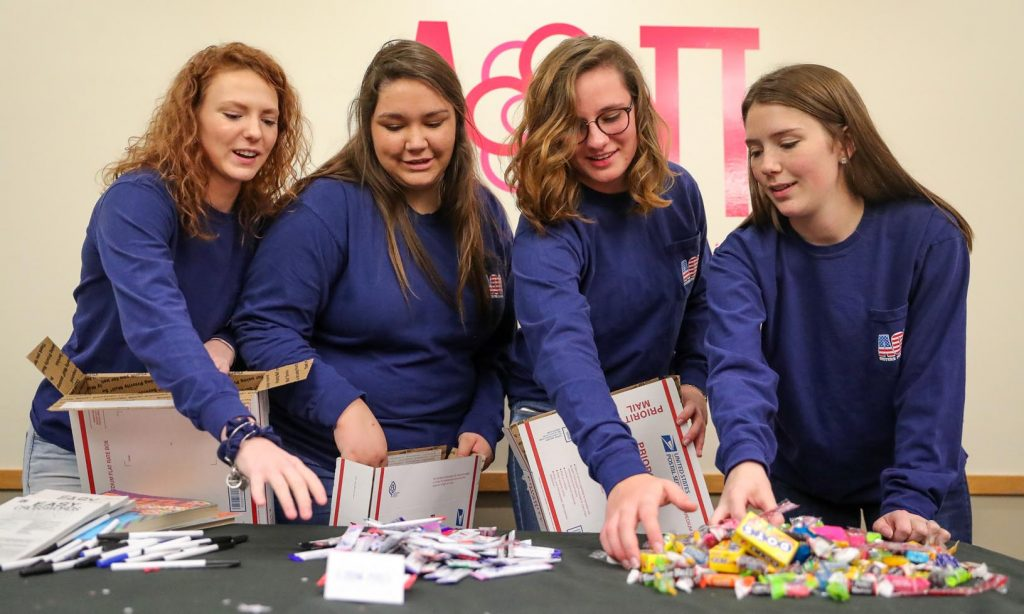 Alpha Omicron Pi members, left to right, Autumn Hallberg of Seward, Madison Failla of Omaha, Emma Thede of Saint Paul and Katelyn Siebert of McCool Junction fill boxes as part of the sorority's Sisters for Soldiers project. The items are being sent to service men and women spending the holidays away from their families. (Photo by Corbey R. Dorsey, UNK Communications)